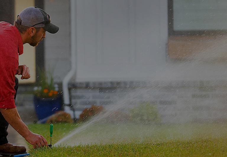 Reddi Technician Repairing Water Sprinkler in Yard